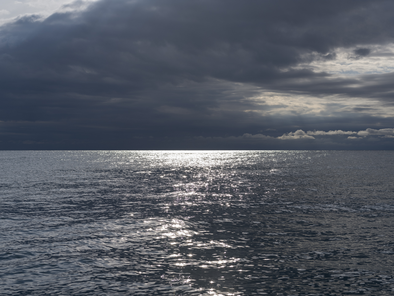 heavy and dark clouds cover a lake with silvery sun