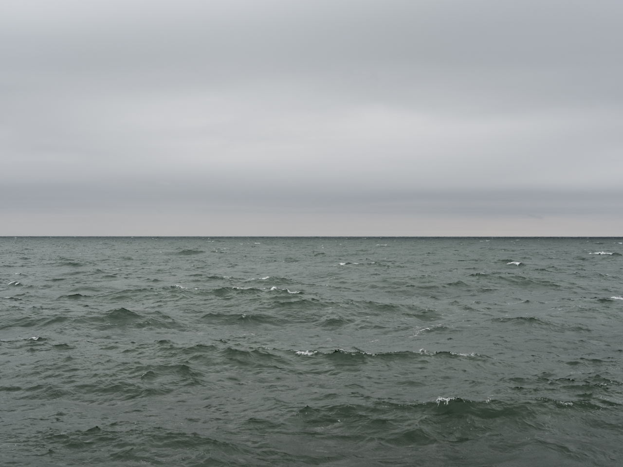 a green Lake Michigan with heavy diffuse cloud coverage