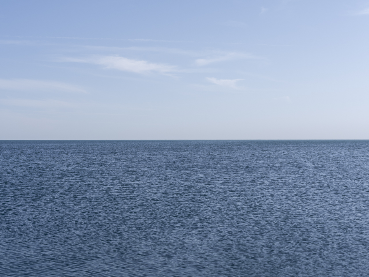 an almost unmoving lake with a few clouds in a light blue sky