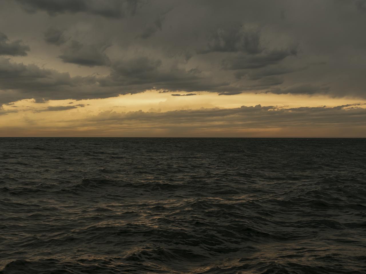 a dramatic dark lake and sky with hazy yellow light