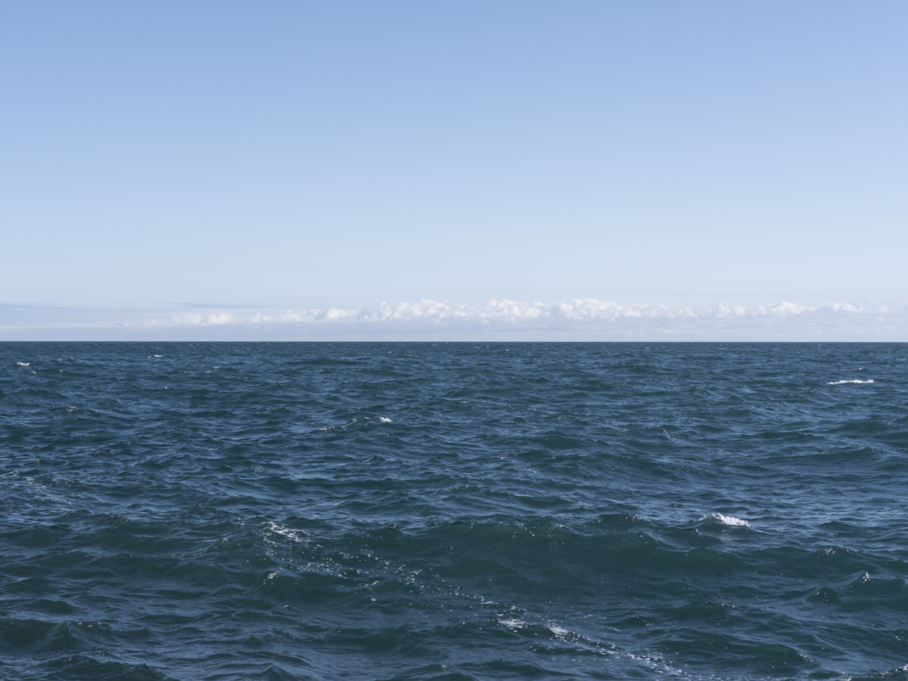 a light blue clear sky with clouds on the horizon of a windy day on Lake Michigan