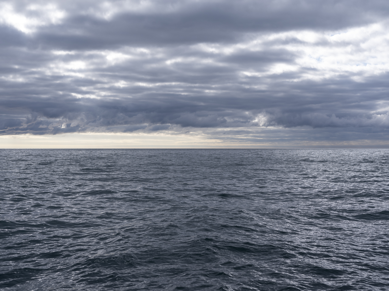 a storm settles over lake michigan with heavy clouds and deep blue water