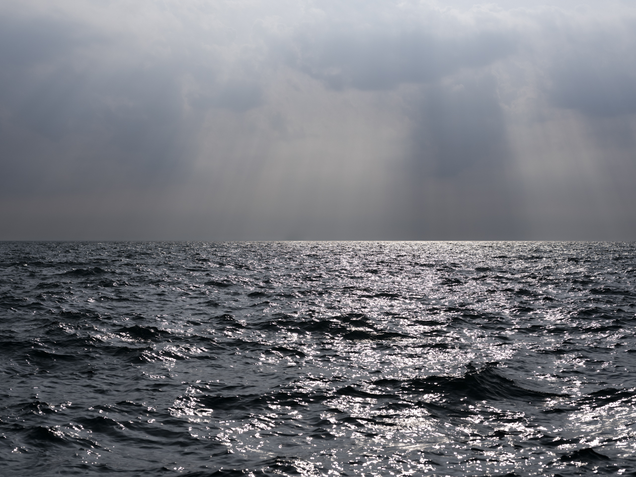 sun streams through heavy clouds over a very dark and roiling Lake Michigan