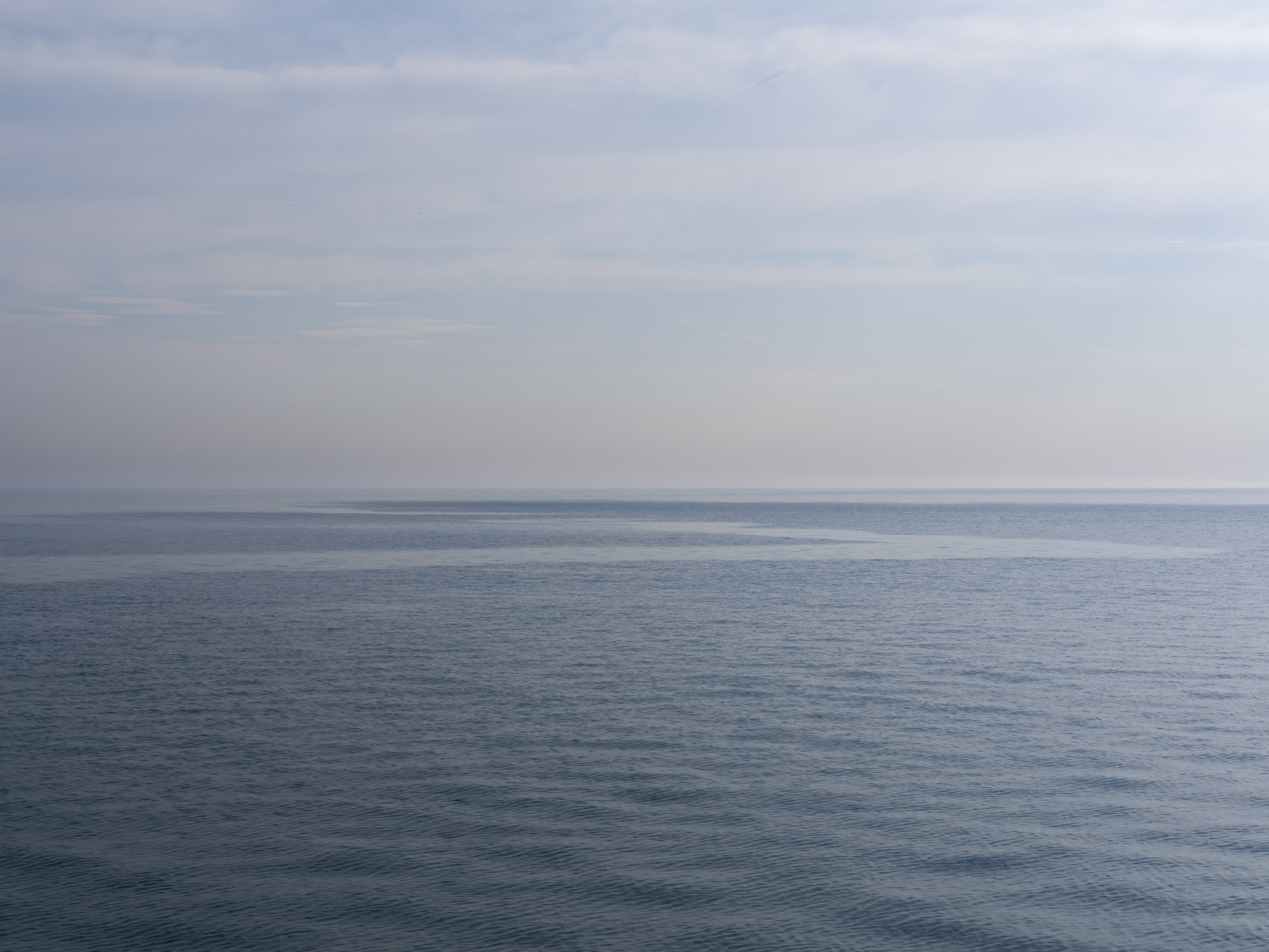 blue overcast sky and an almost entirely still Lake Michigan
