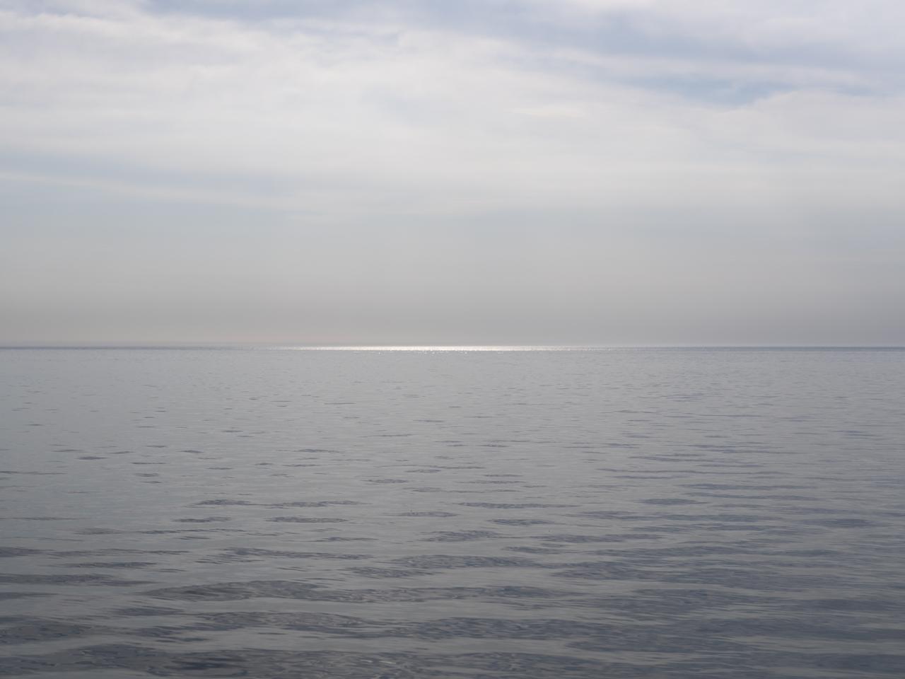 a sliver of light hits the water at the horizon of Lake Michigan