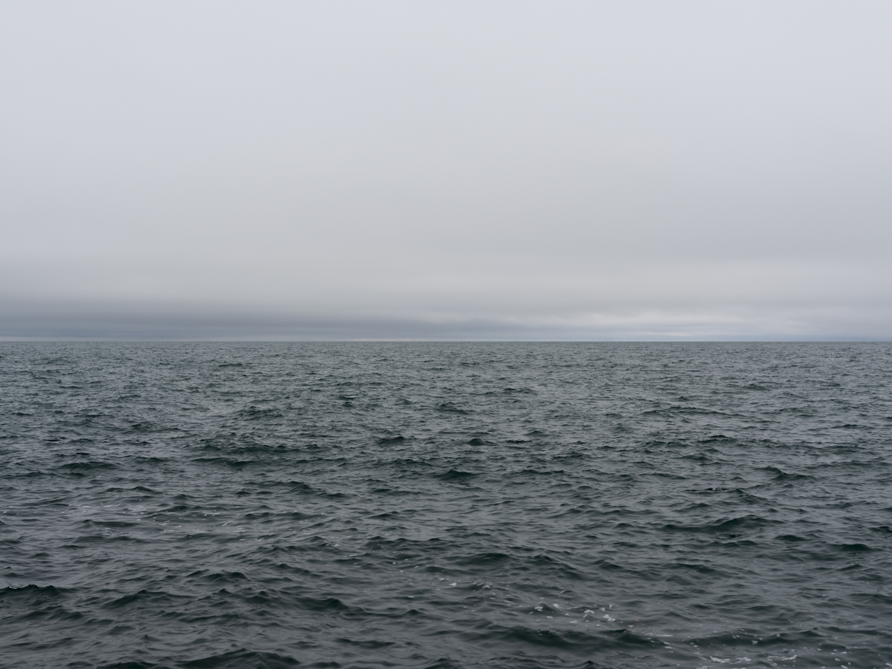 an almost textureless blue cloudy sky over Lake Michigan