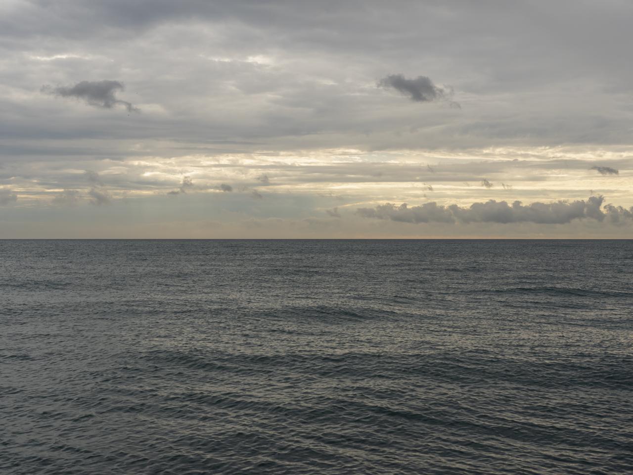 sunlight peeking through heavy clouds over Lake Michigan