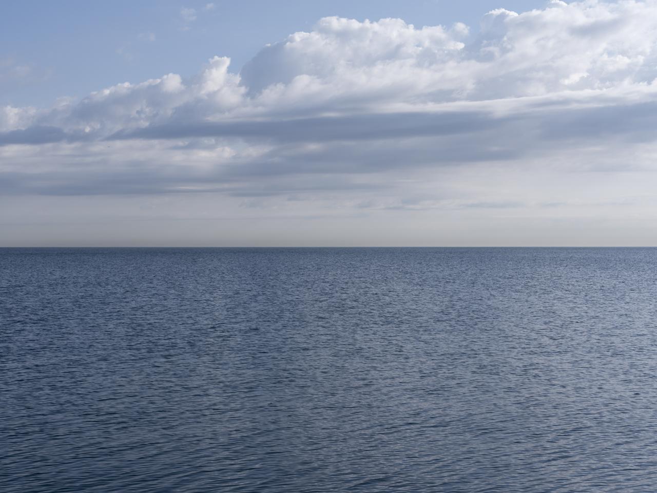 clouds in a blue sky over a still lake michigan