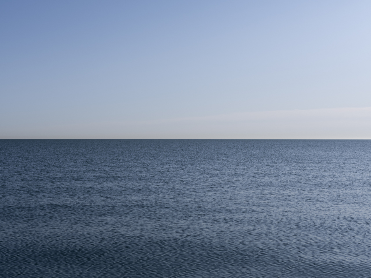 a still blue day with no clouds and slight waves in the water