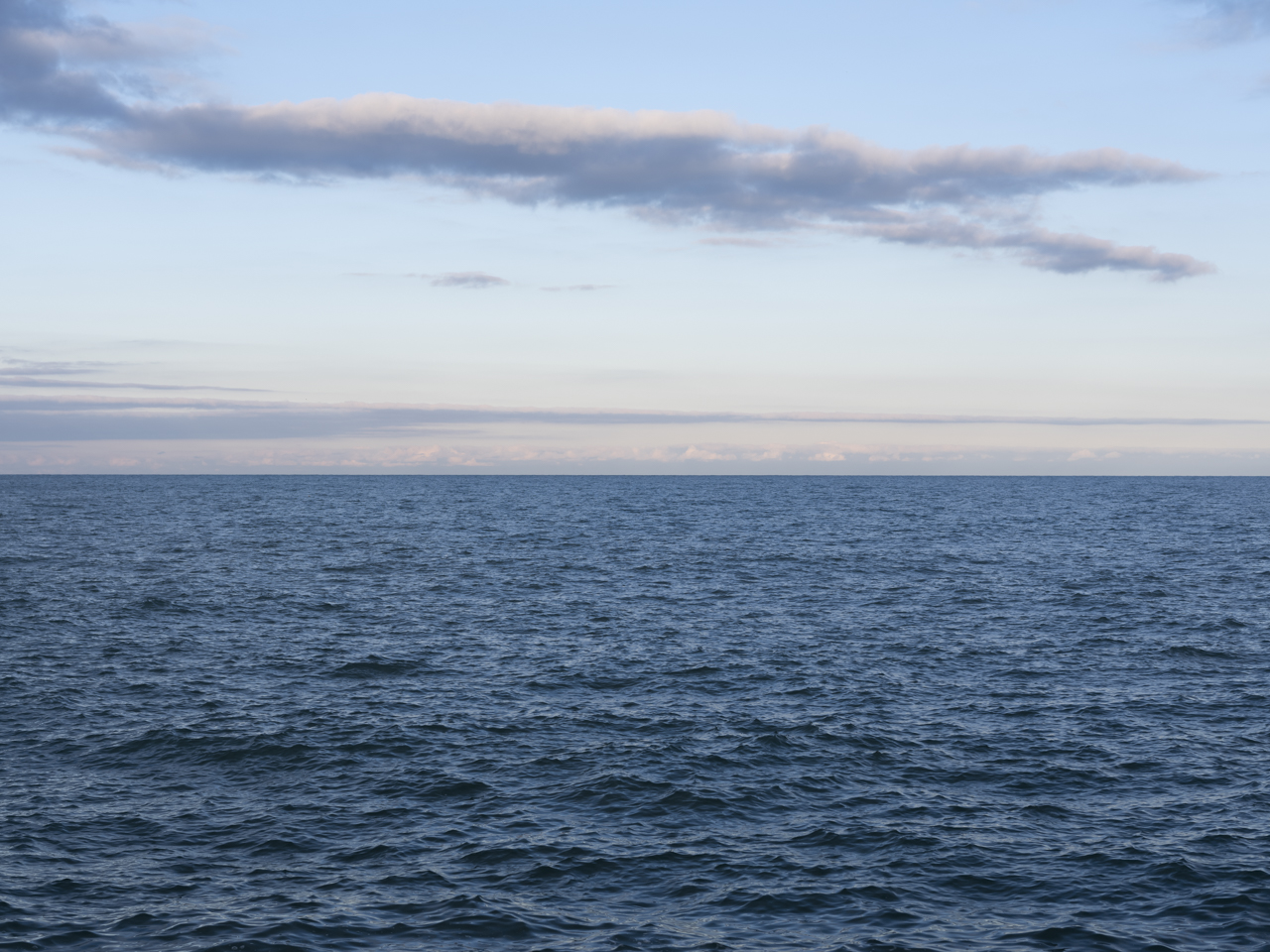 a pastel and blue sky with a horizontal cloud over Lake Michigan