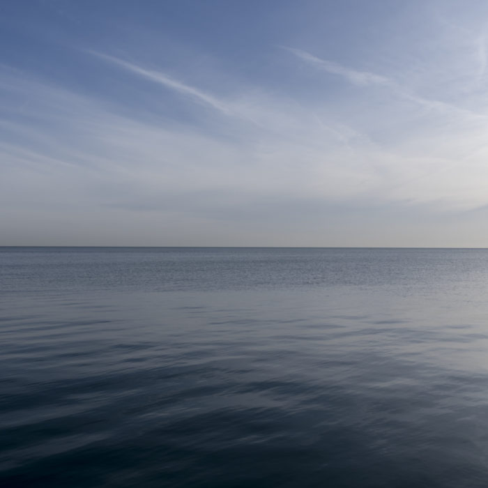 Fine Art Photography of Lake Michigan still flat water with intense morning light and thin clouds from Chicago by Contemporary Photographer Lincoln Schatz