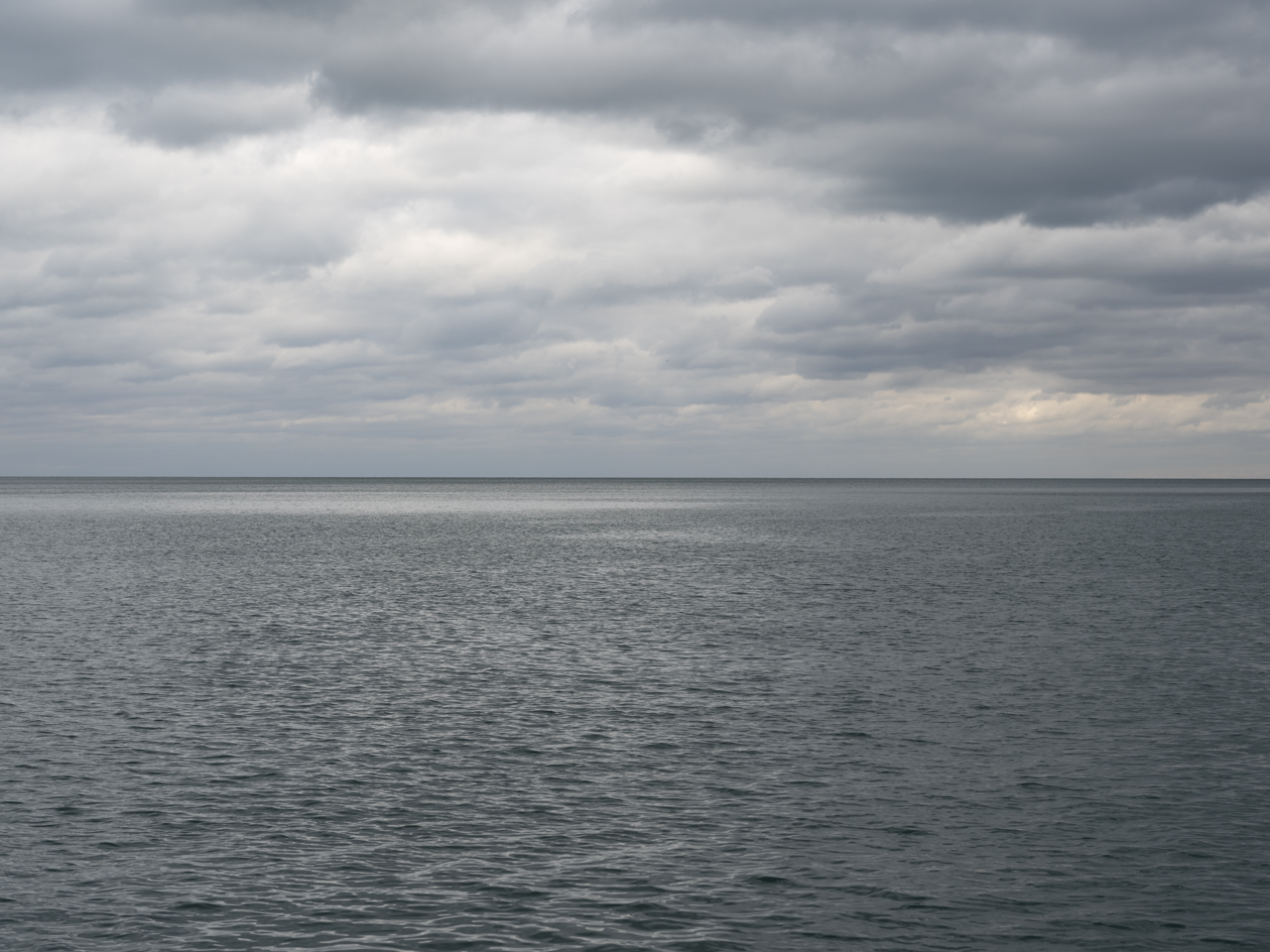 a mostly monotone gray morning on Lake Michigan with heavy cloud cover