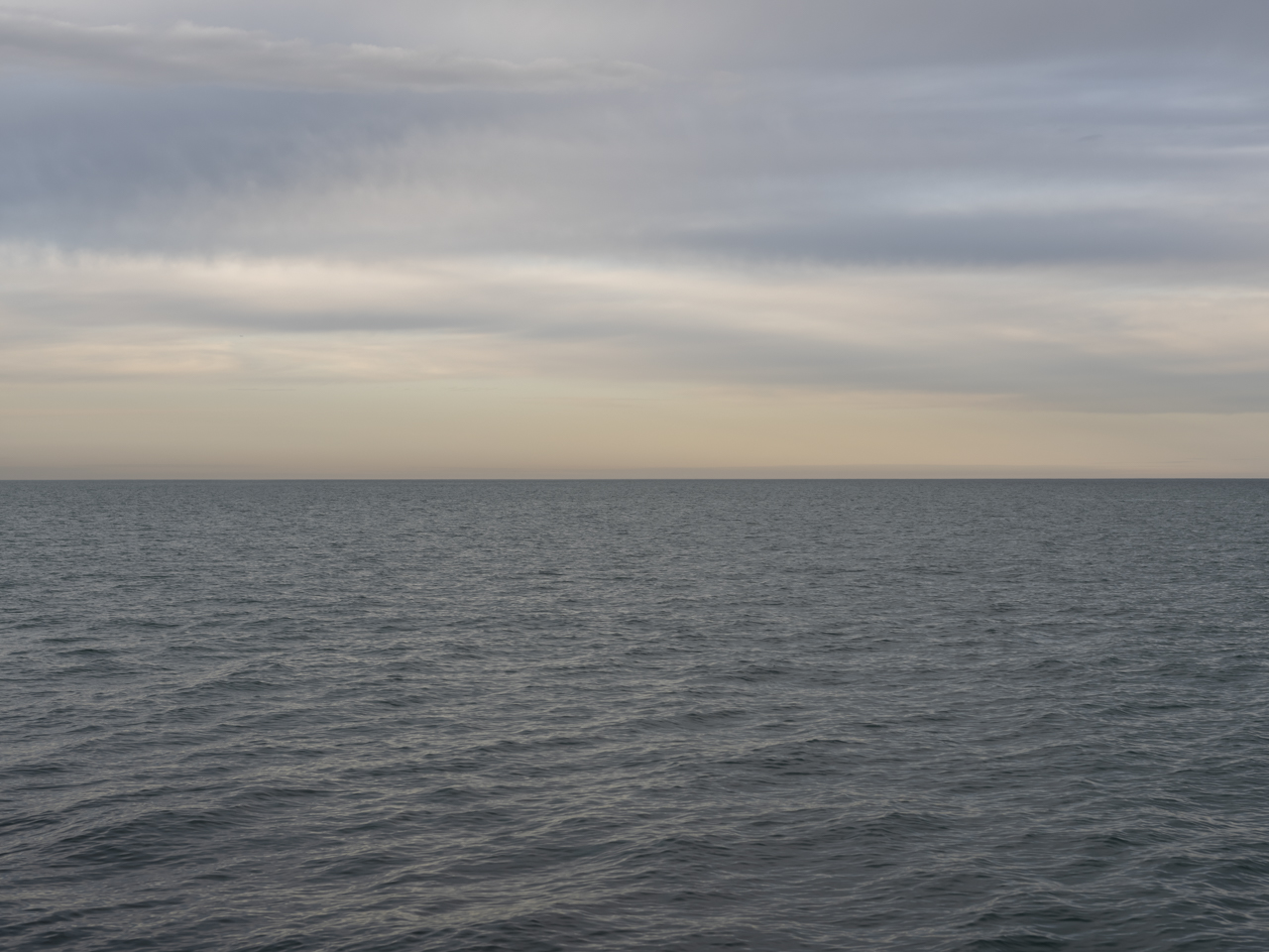 a light gray and yellow morning over Lake Michigan with still water