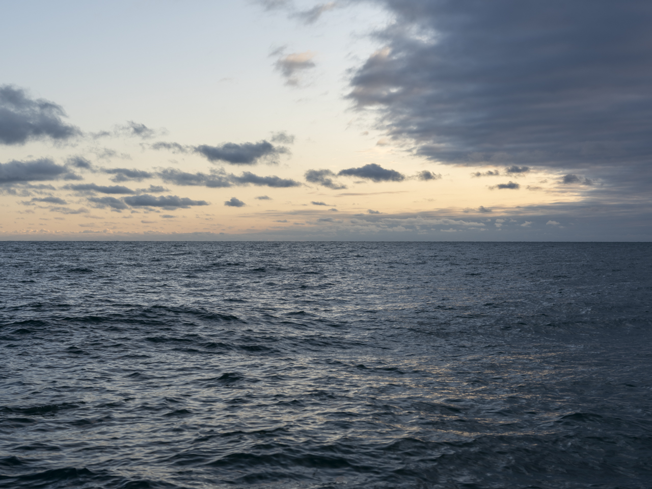 early morning light breaks over the blue waves of Lake Michigan