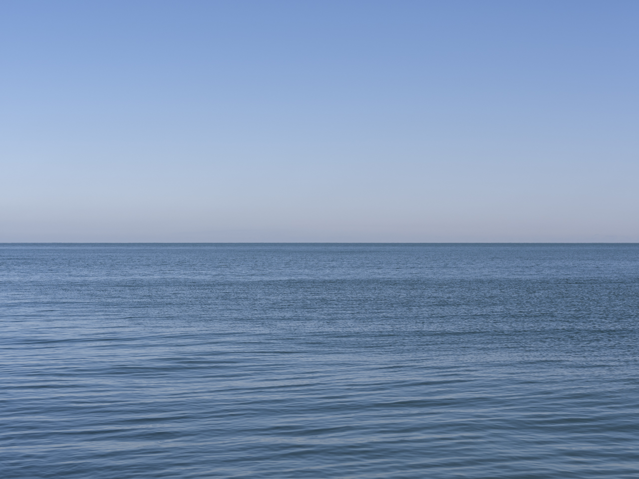 An almost still day with a clear blue sky and water on Lake Michigan
