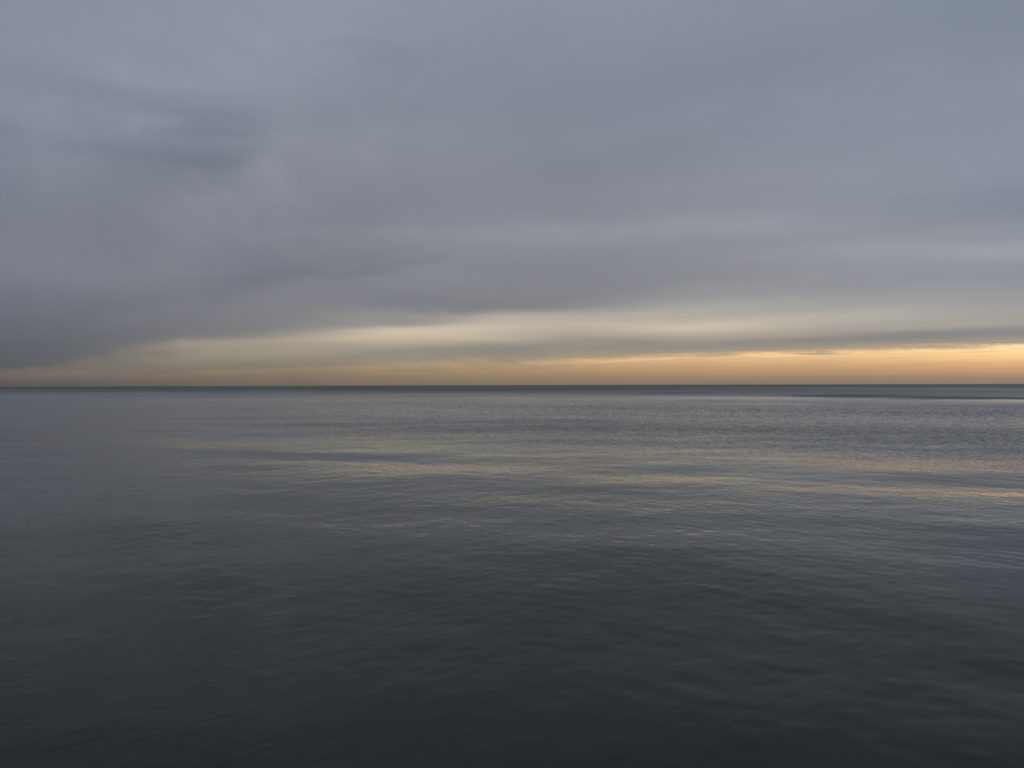 Fine Art Photography of Lake Michigan at sunrise with vidid orange gold against a dark sky and still water from Chicago by Contemporary Photographer Lincoln Schatz