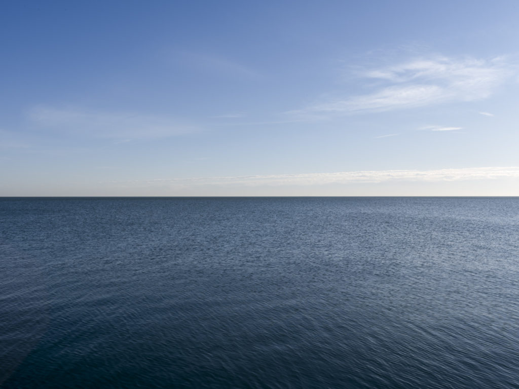 Fine Art Photography of Lake Michigan slight ripple in the water and distant lite clouds from Chicago by Contemporary Photographer Lincoln Schatz