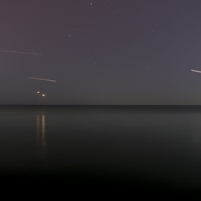 Fine Art Photography of Lake Michigan at night with planes on approach to O'Hare and stars from Chicago by Contemporary Photographer Lincoln Schatz